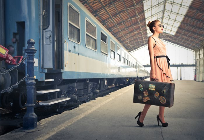 Female traveler with a luxurious vintage suitcase at a train station